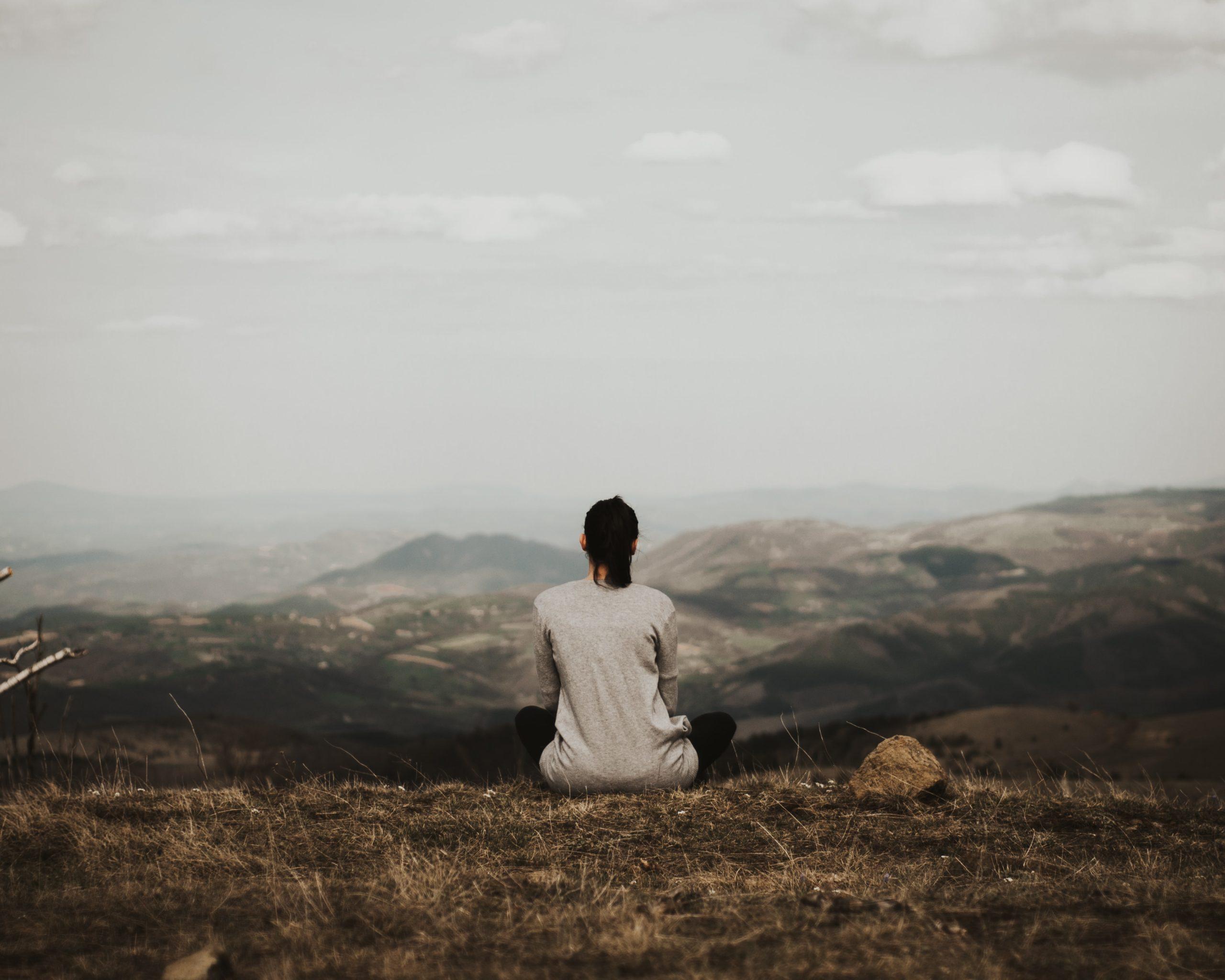 Femme assise face à un paysage